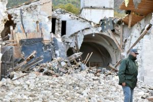 An officer of the State Forestry Corp national police stands in front of a collapsed church in Campi di Norcia, central Italy, October 27, 2016. REUTERS/Emiliano Grillotti