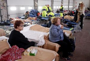 People take a rest after an earthquake in central Italy in a hangar used for recovery in Camerino, Italy October 27, 2016. REUTERS/Max Rossi