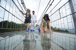 PINGJIANG, CHINA - SEPTEMBER 24:  (CHINA OUT) Tourists walk on a suspension bridge made of glass at the Shiniuzhai National Geological Park on September 24, 2015 in Pingjiang County, China. The 300-meter-long glass suspension bridge, with a maximum height of 180 meters, opened to the public on Thursday.  (Photo by VCG/VCG via Getty Images)